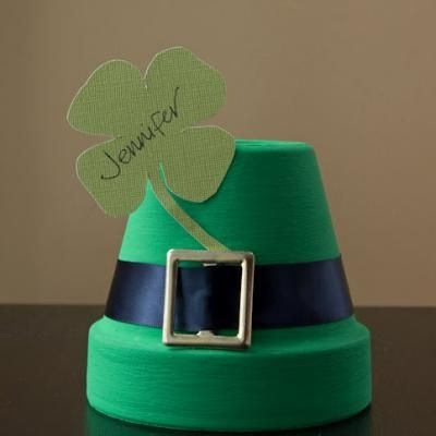 St. Patricks Day Placecard {St. Patrick's Day Party Decor}  Turn a clay pot into a leprechauns hat with this fun St. Patrick's Day tutorial.  This easy DIY craft can be used to decorate your garden or your table for St. Patrick's Day.  And if you are hosting a party, slap a four leaf clover on for luck and add your guests names to turn these cute pots into perfect party place cards