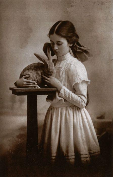 Girl cuddling rabbit, circa 1909