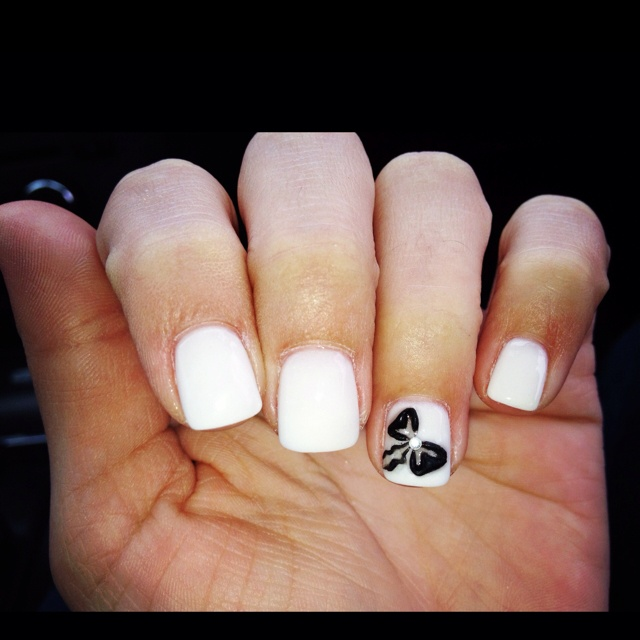 White solar nails with black bow design.