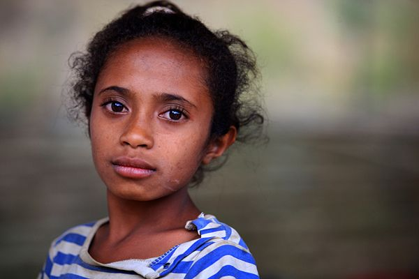 """CAN YOU SEE ME? -- """"Every day, we spend three hours collecting and carrying water,"""" said Elezete (age 9), who lives in the rural village of Mate Restu in Timor-Leste. She rises each morning at 5 a.m. to begin the first of several 30-minute treks she makes daily to the nearest water source, an unprotected mountain spring. She then walks 90 minutes to school, frequently arriving late and tired. Fetching water often falls to girls in Timor-Leste. © UNICEF/James Alcock www.unicef.org/photography"""