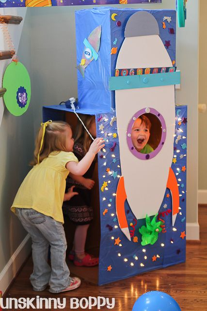 DIY Rocket ship photo booth.  Use a few cardboard boxes covered in blue plastic tableclothes and spraymount a foamcore rocket ship on front.  Cut a porthole in front and decorate with paper, stickers and a strand of Christmas lights.