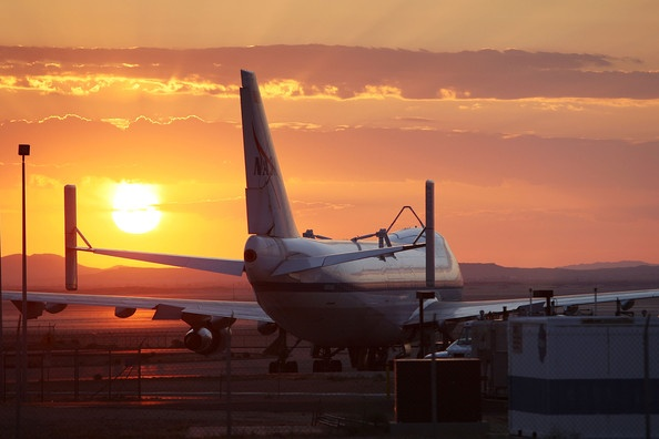 sun rises behind Boeing 747.