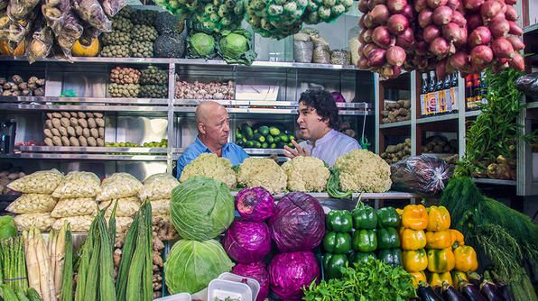 """Andrew & chef Gaston Acurio stand in a """"sea"""" of fresh produce at Surquillo Market in Lima, Peru."""