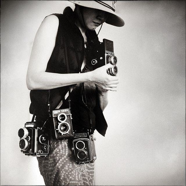 fotógrafa con muchas cámaras colgadas de su hombro.