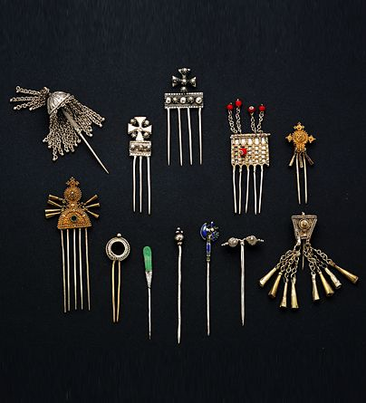 Africa | A collection of hairpins from Ethiopia | Silver, gold-plated, beads | 20th century | Ethiopian women often wear hair pendants with conical bells to set off their intricately plaited hair. Rancid butter, used chiefly as a cosmetic by the Ethiopians, gives the hair its sheen. Haircombs are worn on special occasions. Finely granulated and often gold-plated, these show the influence of Yemeni Jewish goldsmiths.
