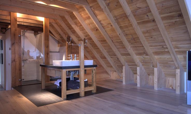 badkamer op zolder. Ruime, rustieke badkamer van hout, steen en glas.