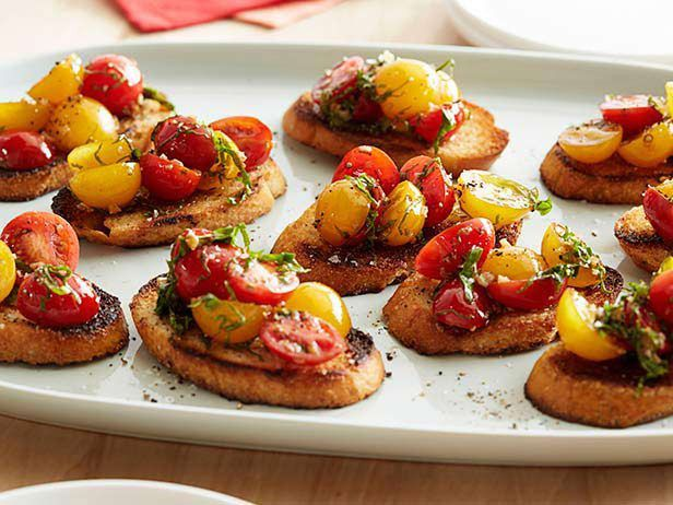 The Pioneer Woman's Party-Ready Bruschetta: Buttery, golden-brown toast is the base of Ree's top-rated bruschetta, topped with garlicky tomatoes and fresh basil to create a simple appetizer. #RecipeOfTheDay