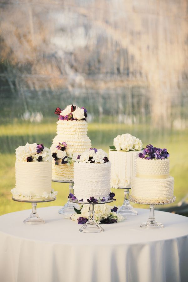 multiple wedding cakes // white ruffles, purple flowers, glass cake stands