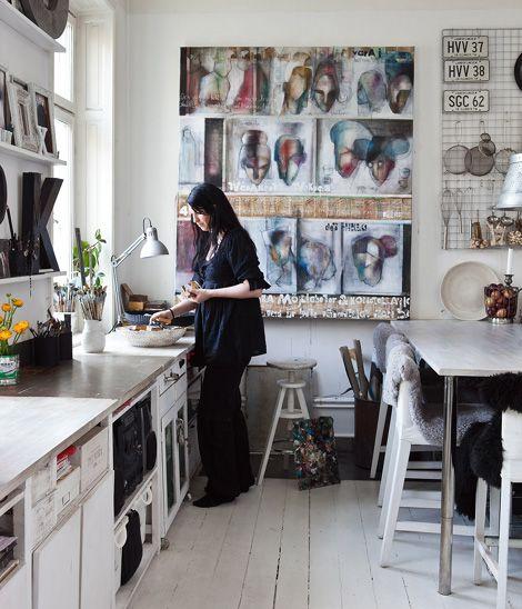 Una cocina en blanco llena de arte y objetos.  Frente cuadros