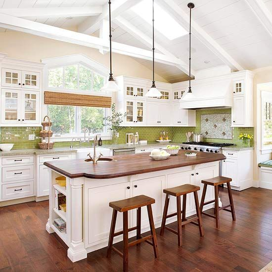 Green kitchen back splash A soaring ceiling leaves this kitchen feeling bright and open