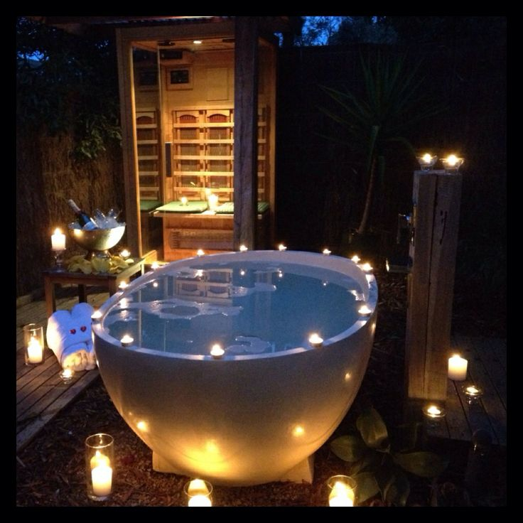 In a luxurious outdoor candle lit bath a place of sanctuary in nature
