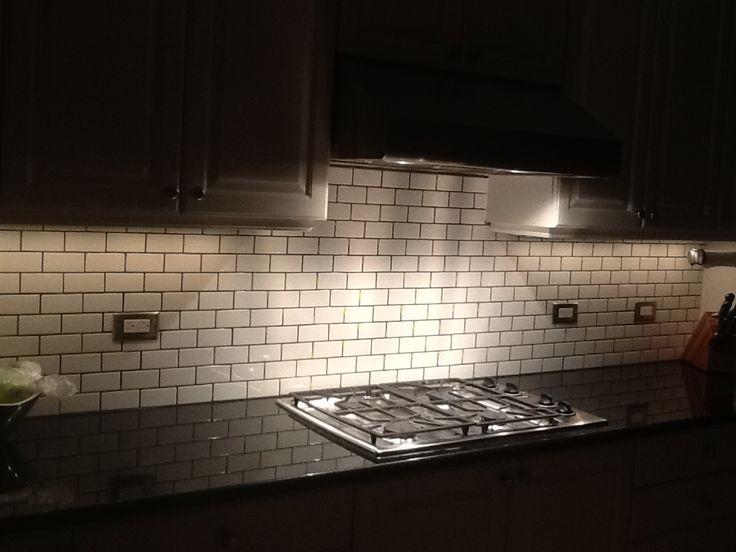 2x4 white subway tile dark gray grout xenon under cabinet lighting