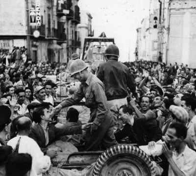 Residents cheer and greet troops entering the freed city of Monreale. Italy, 1943. (Robert Capa)