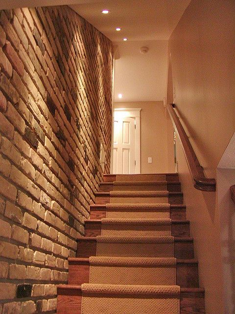 love the brick wall lighting and runner on the basement stairs