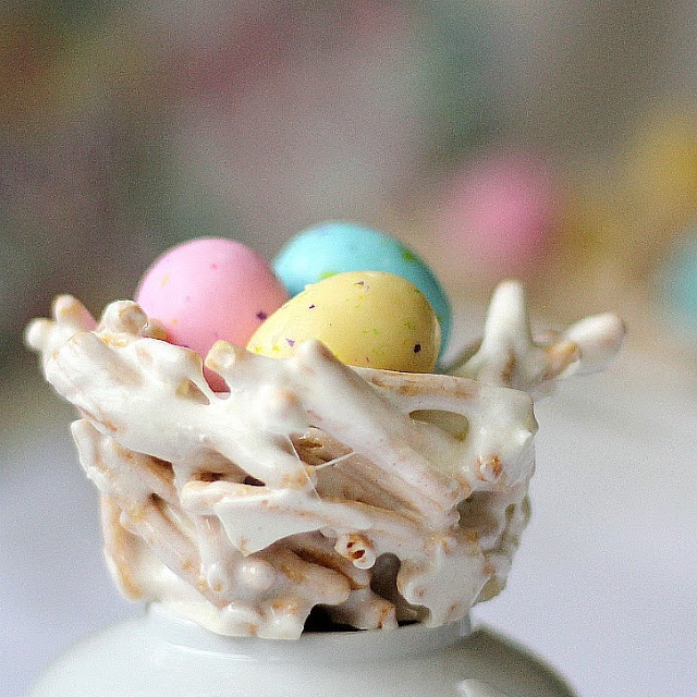 Easter bird's nests with pretzels, marshmallows, and speckled chocolate eggs. Shaped in a muffin tin.