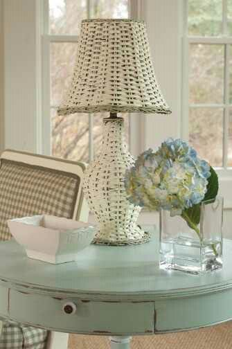 This is a great example of cottage interior. It has a wicker lamp, light blue wood table, and white with checkered furniture. This mixing idea is common for this style.
