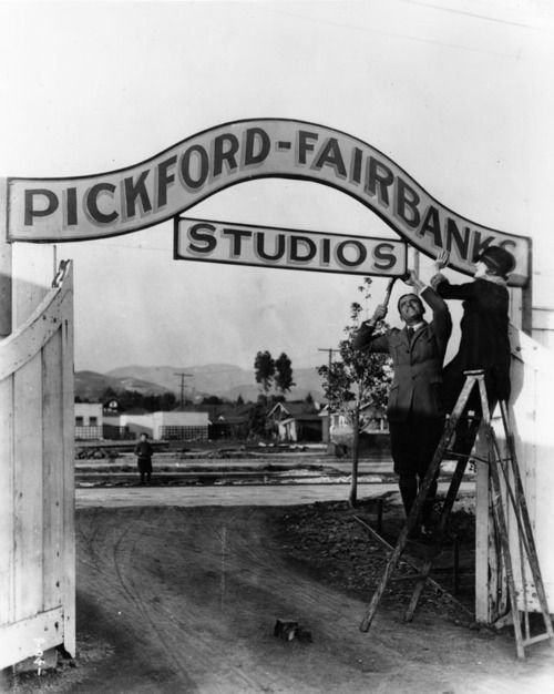 Douglas Fairbanks and Mary Pickford hang the sign for their Pickford-Fairbanks Studio in Hollywood, CA - 1922