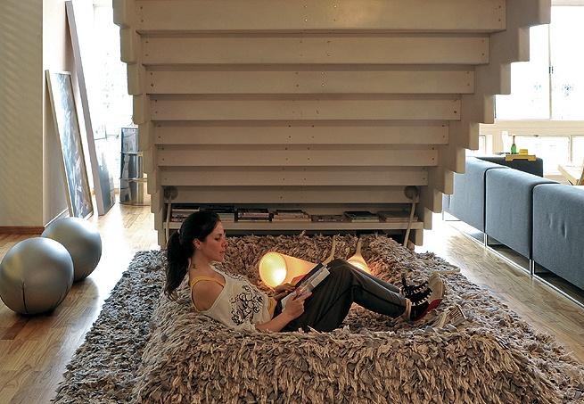 Geralmente perdida, a área embaixo da escada pode virar um canto aconchegante e até servir de espaço para leitura. Repare que o fundo de um degrau virou prateleira para livros e revistas.