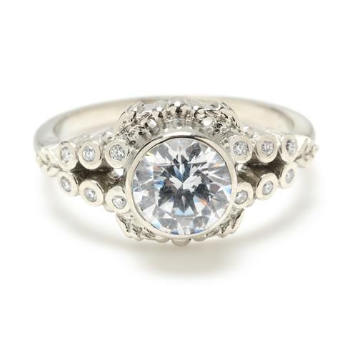 This baroque 18k white gold band has two sets of diamond stones that converge at the beautifully detailed bezel-set center diamond.  at Greenwich Jewelers