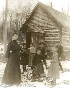 hand-printed, sepia toned photograph. printed in a darkroom, using a 4x5 negative, made from the original image. This photo shows teacher with her students, in front of a rustic, one room schoolhouse in the U.P. of Michigan.