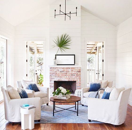 Rugs 101: Your Ultimate Guide to Rug Shopping // blue area rug, white slip cover arm chairs, blue throw pillows, brick fireplace