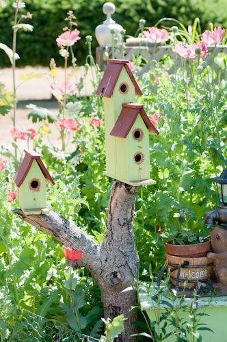 A trio of delightfully cute little wooden birdhouses perched atop a tree branch. #birdhouse #garden #yard #backyard #birds #summer