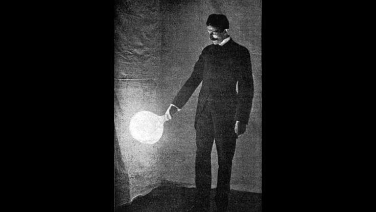 Nikola Tesla holding a light bulb with his bear hand which ...