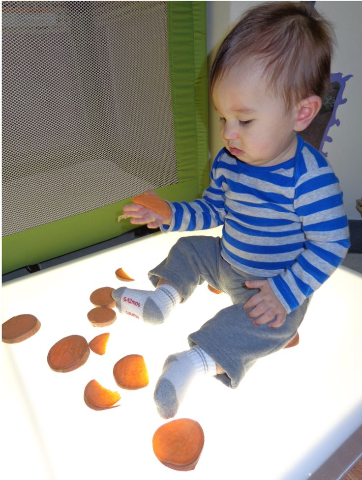 Infant Plays With Sweet Potatoes On Light Board To Expand