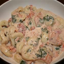 Cheese tortellini are served in a creamy tomato and spinach sauce.