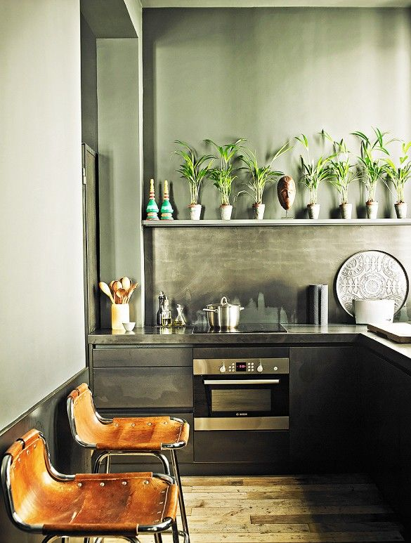 Dark industrial kitchen with leather stools and plants.