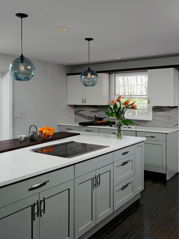 Two orange pendant lights balance the length of the kitchen island and