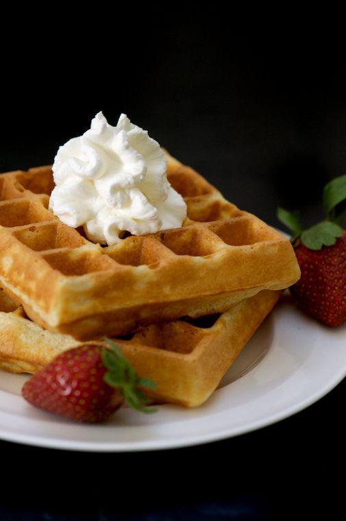 Belgian waffles with strawberries, honey, and fresh whipped cream