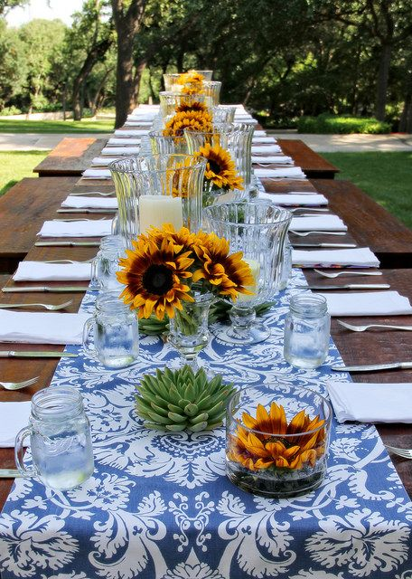 Outdoor summer table with blue and white runner and sunflowers.