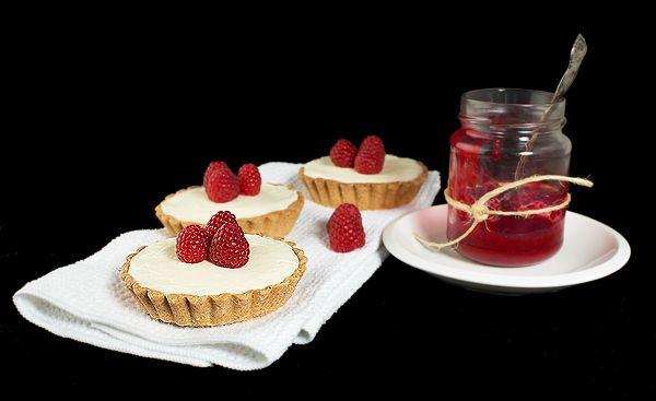 ... White Chocolate Raspberry Tarts displayed with homemade raspberry jam