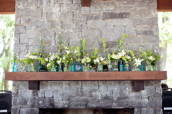 flower vases galore on the fireplace mantle. decorations ~ glass ~ blue and green and yellow.
