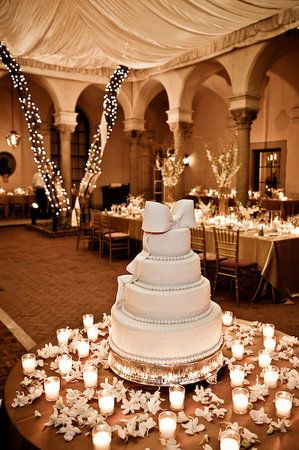 cake with a bow on top & candles surrounding it.