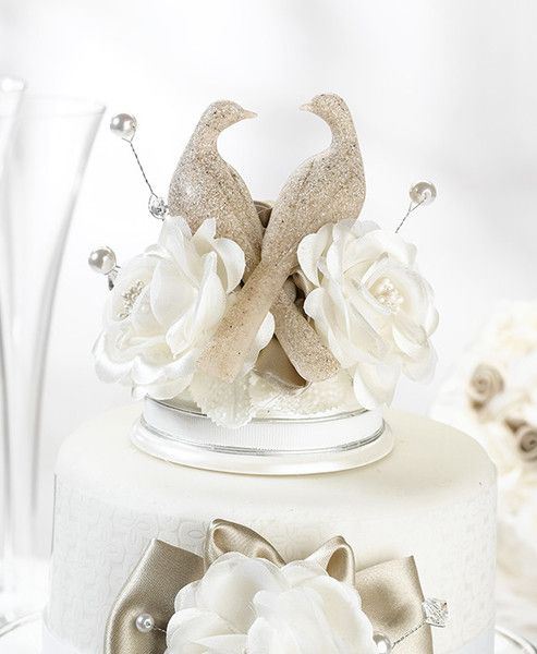 "This elegant caketop features a pair of doves sharing a loving glance. The doves are resin with a faux stone finish. Below the doves are a series of beads, as well as flowers in taupe and ivory colors. The off-white resin base has a flat bottom for easy placement on the wedding cake. Size: 5"" tall, with a base diameter of 3.5""."
