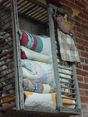 Old Weathered Wood Chicken Cage...stuffed with old quilts.