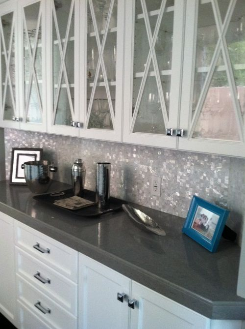 white cabinets solid grey counter and mother of pearl backsplash