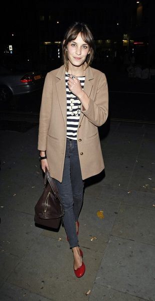 Alexa Chung - Tan single breasted peacoat, breton stripe shirt, washed blue/grey skinnies and red flats.