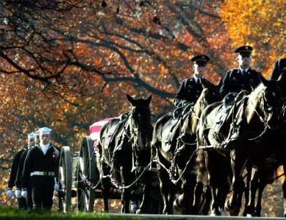 Military honor guard escorting a horse drawn carriage during funeral