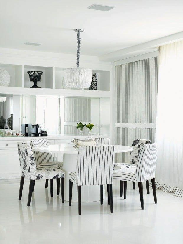 """Para a decoração deste apartamento em Higienópolis, São Paulo, a designer de interiores Neca Abrantes escolheu uma paleta de cores claras e sóbrias. Na sala de jantar, a designer abusou do contraste entre o preto e o branco. Para deixar o ambiente com um ar mais leve, há um mix de estampas: listras e florais. O espelho integrado ao aparador  é também um elemento que ajuda a """"aumentar"""" o espaço. A decoração é feminina e moderna. A soberania do branco garante ao espaço e um agradável frescor."""