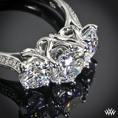 """Elegance is redefined with this magnificent 3 Stone """"Swan"""" Diamond Engagement Ring. The graceful lines twist and swirl to create an extraordinary sanctuary for your diamonds, which will allow for maximum exposure and total security. The sides of the shank sparkle with 36 Round Brilliant Diamond Melee"""