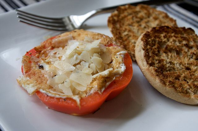 egg with in a slice of bell pepper and topped with parmesan cheese