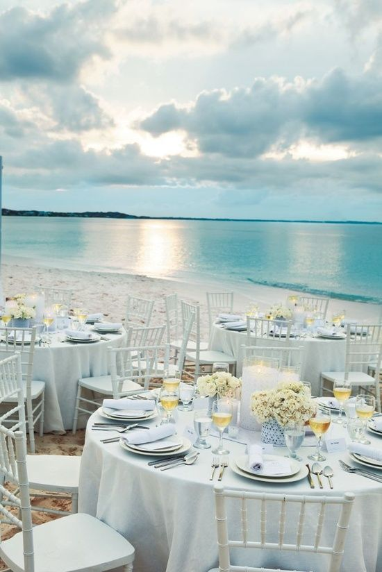 White Linen Wedding Table Setting by the Beach... breathtaking! Pin to #Win! Who needs blue table accents when all the blue you need is in the background?! I want to frame