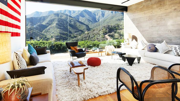 Real Estate Envy: 7 Dreamy Vacation Homes // living room, shag rug, cane chair, red pouf, wing chair, American flag, Santa Barbara