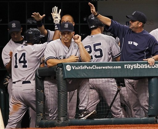 GAME 81: Wednesday, July 4, 2012 - New York Yankees' Curtis Granderson (14) and Mark Teixeira (25) are congratulated behind manager Joe Girardi, center, after scoring during the eighth inning of a baseball game against the Tampa Bay Rays in St. Petersburg, Fla. The Yankees won 4-3.