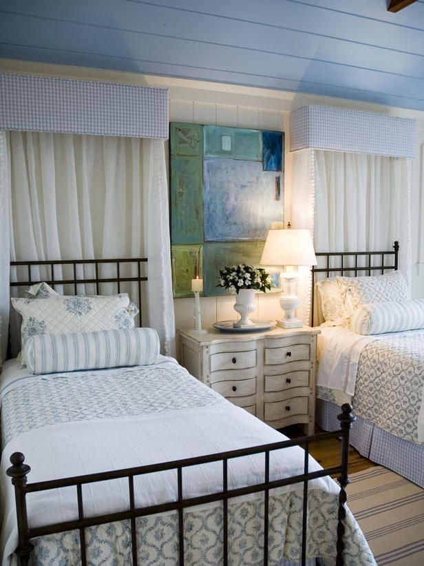 The outdoor-inspired and cottage-style living of HGTV Dream Home 2006 was gracefully extended into the guest bedroom suite. Designer Linda Woodrum gave rustic, wrought iron beds a dreamy touch with matching cornice boards and sheer white fabric.