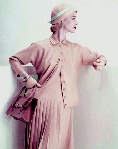 1955    Model is wearing an amber suit of linen rayon, a long torso jumper with a knife pleated skirt and a hip long jacket by Majestic.