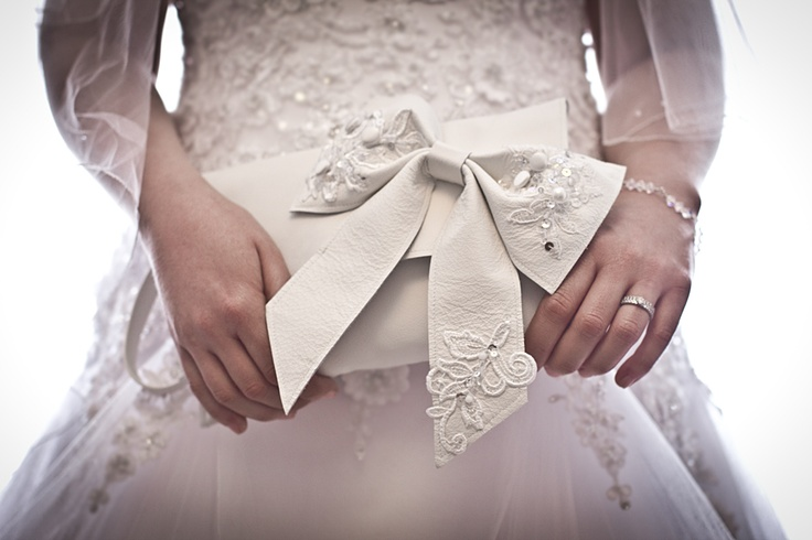 Beautiful bespoke brides bag in soft white leather. Embellished with a leather bow incorporating lace & buttons from her own gown & her mother's wedding dress. www.dazeddorothy.co.uk